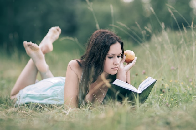 Attentive girl with apple lying on the green grass and reading a book. the concept of a healthy lifestyle