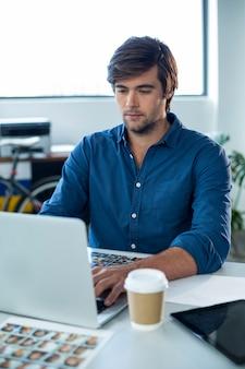 Внимательный графический дизайнер работает на ноутбуке