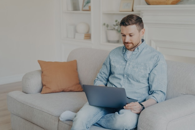 Attentive handsome young man in casual clothes using laptop during leisure time while sitting on sofa at home, looking for his favorite tv shows online to watch over weekend