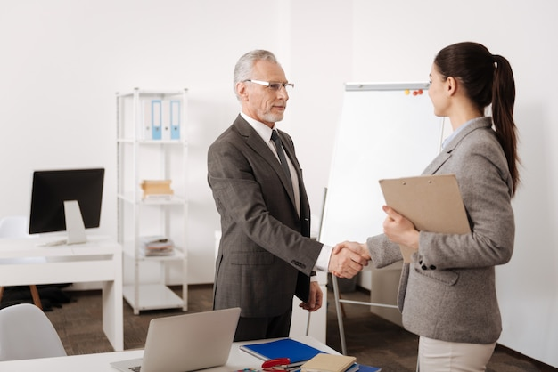 Attentive kind employee keeping smile on face standing in semi position while looking at his colleague