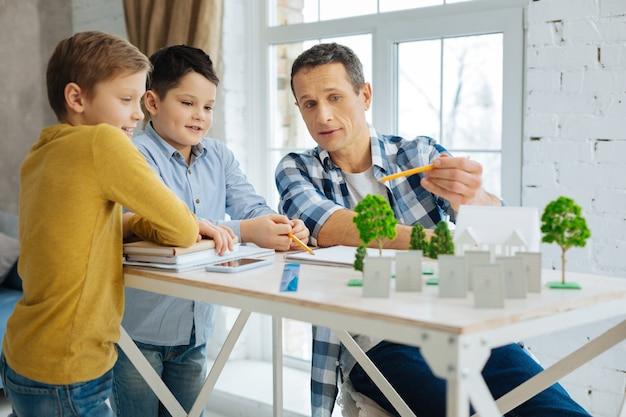 Внимательные слушатели. красивый молодой архитектор объясняет свой проект ландшафтной архитектуры эко-города своим сыновьям во время их посещения его офиса, пока мальчики внимательно слушают