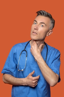 Attentive male doctor touching his neck