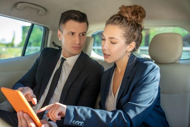 気配りのある男と女の車でタブレットを使用して