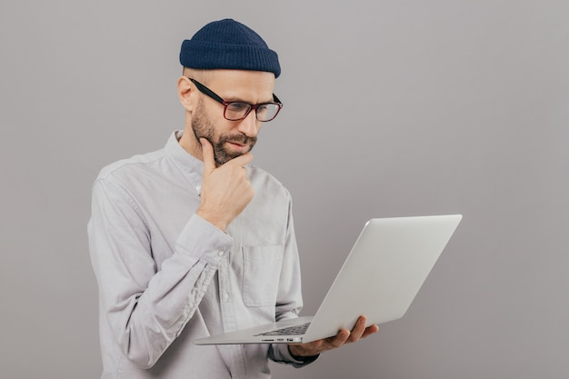 Attentive man holds chin, focused in monitor of laptop computer