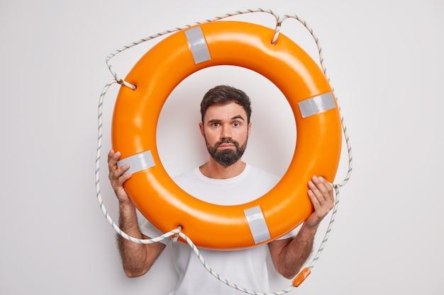 Внимательный спасатель человек смотрит через спасательный круг заботится о предотвращении несчастных случаев, готов спасти людей во время чрезвычайной ситуации, позирует у белой стены