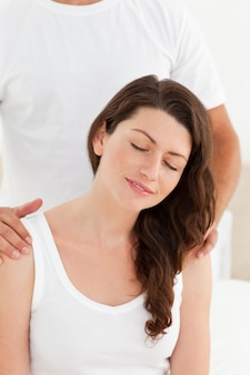Attentive man massaging his girlfriend's back sitting on their bed
