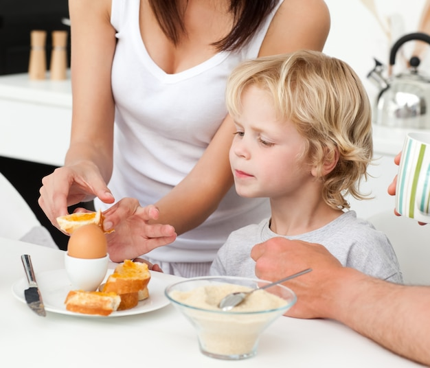 Attentive mother breaking a boiled egg for her son during breakfast