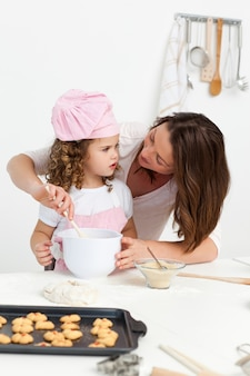 Attentive mother learning her daughter how to cook