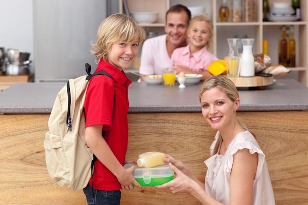 彼の息子に学校の昼食を詰めている気配の母