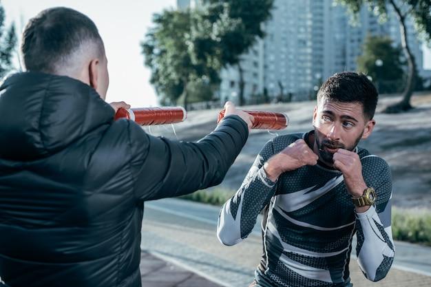 総合格闘技のトレーニングを受けながらボクシングのスティックを見ている気配りのあるプロスポーツマン