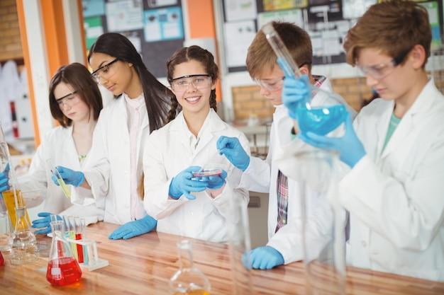 実験室で化学実験を行う気配りのある学校の子供たち