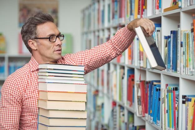 図書館で本を持って親切な学校の先生