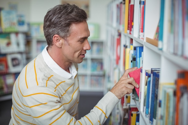도서관에서 책을 선택하는 세심한 학교 교사
