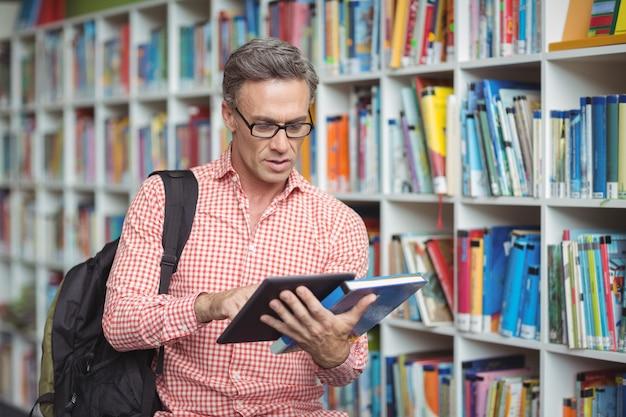 도서관에서 디지털 태블릿을 사용하는 세심한 학교 교사