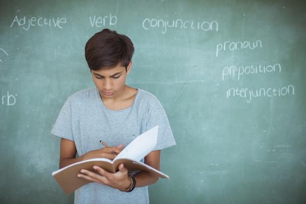 Внимательный школьник читает книгу против классной доски в классе