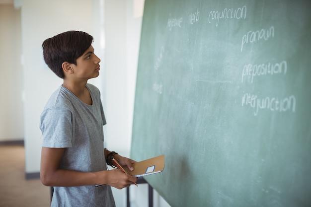 Внимательный школьник читает классную доску в классе