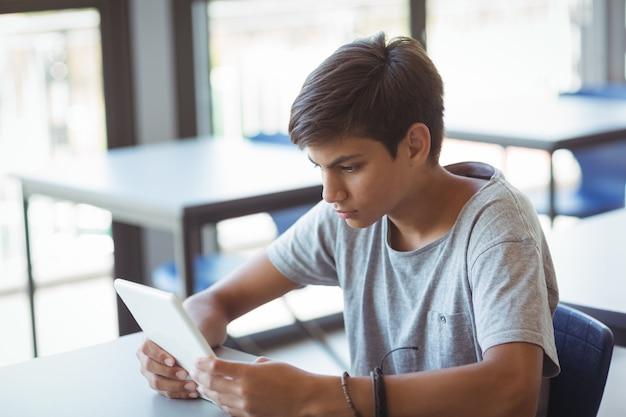 教室でデジタルタブレットを使用して親切な少年