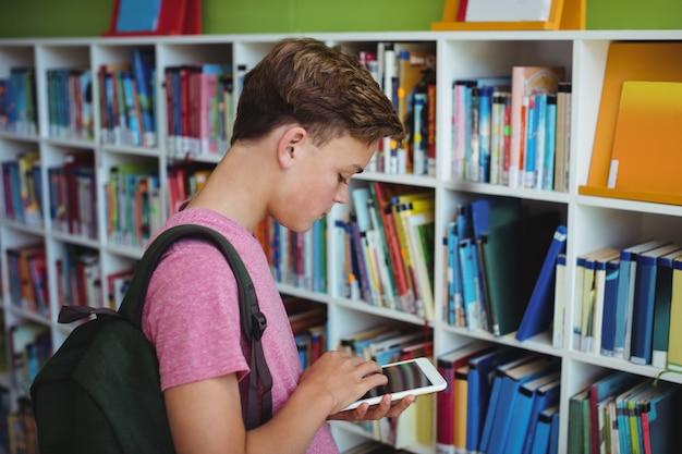 Attentive schoolboy using digital tablet in library