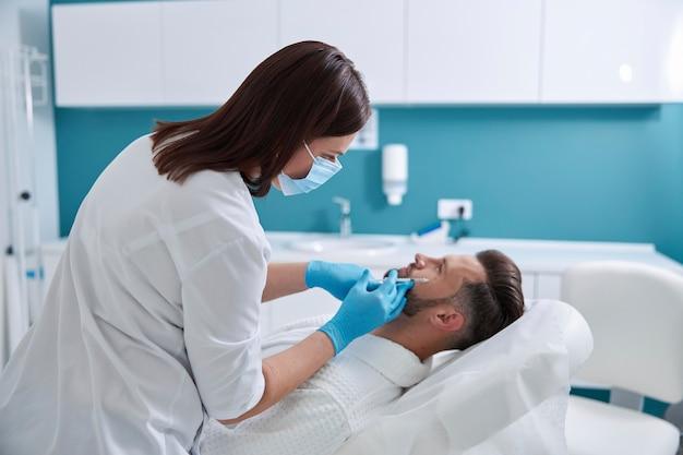 Внимательный косметолог женщина в белой форме делает инъекцию наполнителя для гусиных лапок клиенту