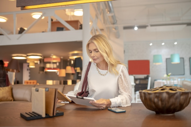 Внимательная женщина держит в руках образцы дерева, сидит за столом в мебельном салоне, размышляет.