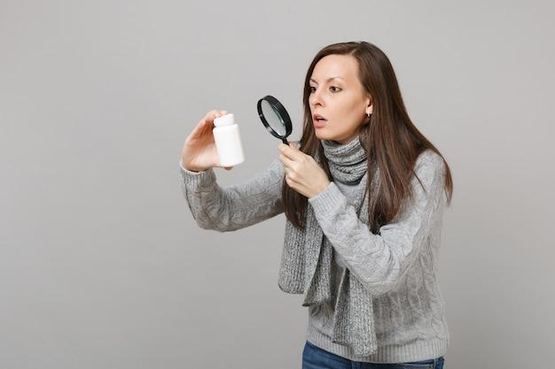회색 배경에 돋보기가 있는 병에 아스피린 알약이 있는 약을 보고 있는 스웨터를 입은 세심한 여자. 건강한 생활 방식, 아픈 질병 치료, 추운 계절 개념.