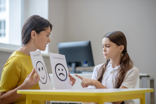 Attentive woman showing pictures with emotions and serious girl choosing one of them