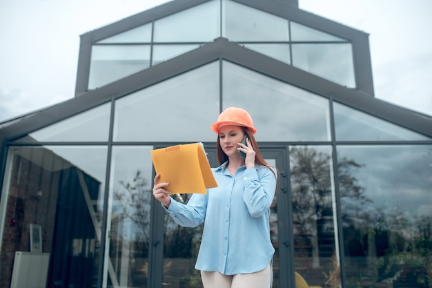 Внимательная женщина с документом разговаривает по смартфону