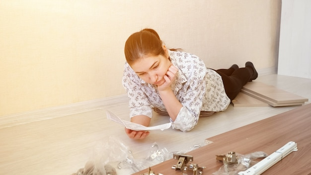 Attentive woman with ponytail lies on tile floor and analyzes guidance note for assembling kitchen cabinet close view