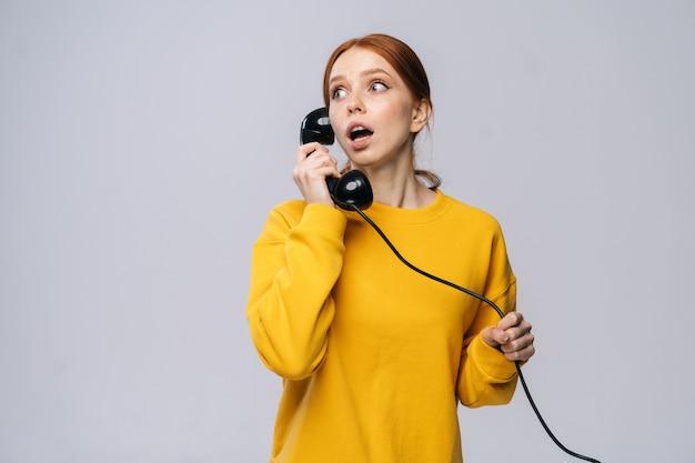 Внимательная молодая женщина в стильном желтом свитере разговаривает по ретро-телефону и смотрит в сторону