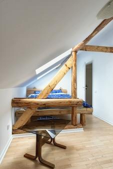 古い素朴な木製の梁と屋根裏部屋のアパートモダンなベッドルームのアパートのインテリアデザイン