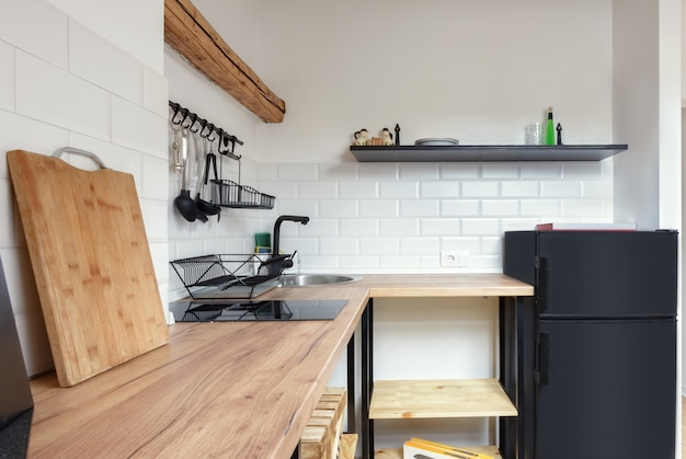 古い素朴な木製の梁と家具を備えた屋根裏部屋のアパートモダンなkitchenapartmentインテリアデザイン