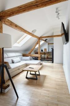 屋根裏部屋のアパート古い素朴な木製の梁とモダンなリビングルームのアパートのインテリアデザイン