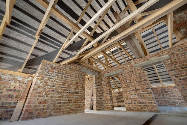 Attic of a building under construction with wooden roof structure and brick walls.