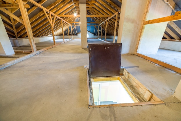 Attic of a building with wooden beams of a roof structure and a fire exit door in floor.