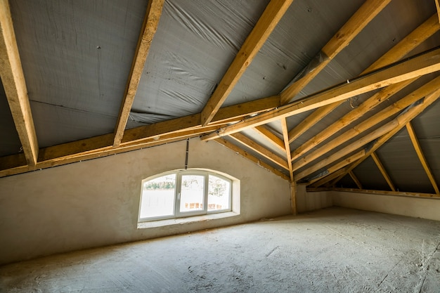 Attic of a building with wooden beams of a roof structure and a small window.