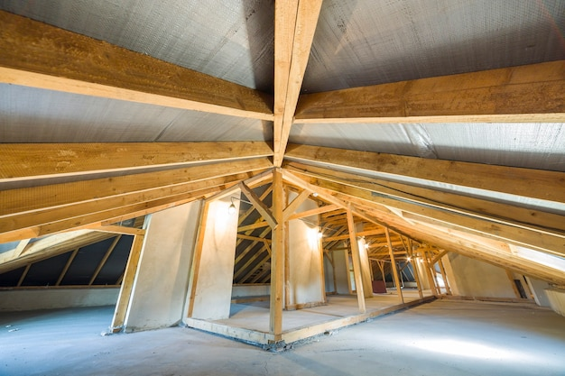 Attic of building with wooden beams of roof structure.