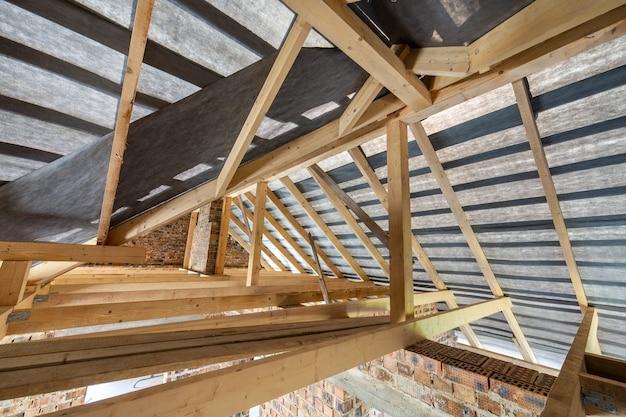 Чердак строящегося дома с деревянными балками кровельной конструкции и кирпичными стенами.