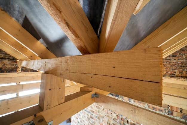 Чердак строящегося здания с деревянными балками конструкции крыши и кирпичными стенами.