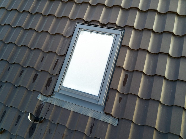Attic plastic window installed in shingled house roof