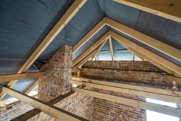 Чердачное помещение строящегося здания с деревянными балками кровельной конструкции и кирпичными стенами. концепция развития недвижимости.