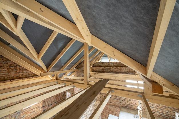 지붕 구조와 벽돌 벽의 목재 들보와 건설중인 건물의 다락방 공간. 부동산 개발 개념.
