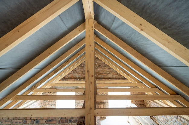 屋根構造の木製の梁とレンガの壁で建設中の建物の屋根裏空間。