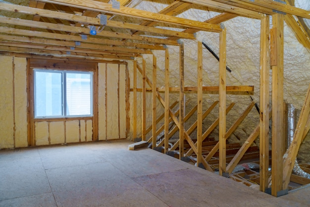 Attic with foam insulation frame house in process of in unfinished under construction