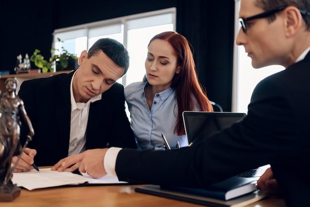 변호사는 결혼 해산 계약서에 서명 할 곳을 보여줍니다.