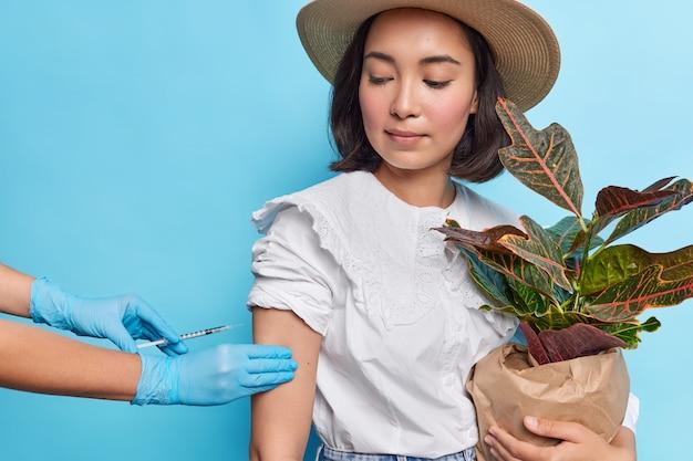 L'attraente signora asiatica con i capelli scuri tiene in mano una pianta d'appartamento in vaso riceve il vaccino in braccio per proteggersi dal coronavirus indossa una camicetta bianca fedora isolata sul muro blu