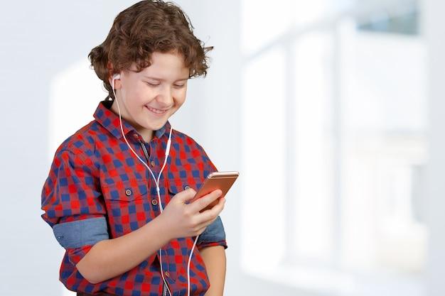 매력적인 아이가 헤드폰으로 음악을 듣고 있다