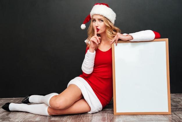 검은 표면 위에 침묵 기호를 보여주는 빈 화이트 보드와 산타 클로스 의상에서 매력적인 젊은 여자