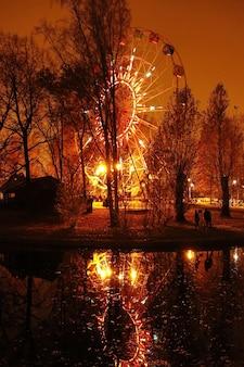 Аттракцион колесо обозрения с огнями в парке развлечений ночью