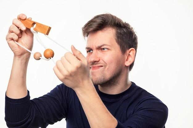 木製のパズルで混乱している魅力的な25歳のビジネスの男性。