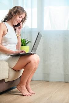 Привлекательная 40-летняя кавказская женщина, улыбаясь в коротком белом платье, удаленно работает со своим смартфоном и ноутбуком с дивана дома